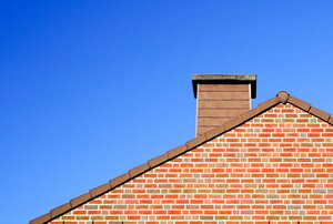 A home roof with a brick chimney extending above it.