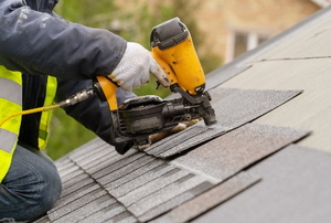 person shingling roof with nail gun