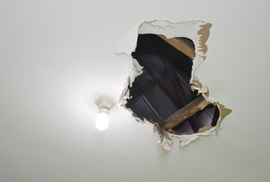 A light next to a hole in a ceiling exposing the framework.