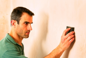 A man sanding a newly painted wall with a hand-held sanding block