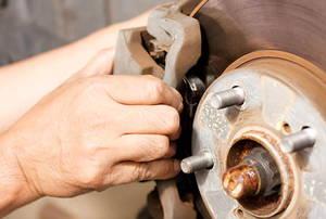 person replacing brake pads