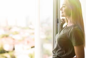 woman by open window with sunlight