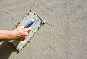 Using a trowel to spread stucco on a wall.