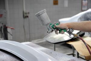 Person spraying automotive paint