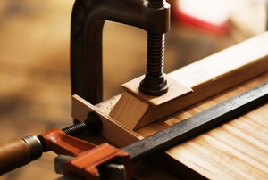 a table clamp holding a piece of wood on a table