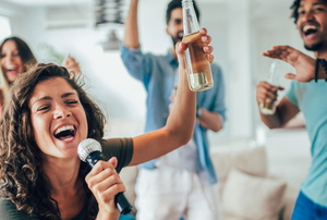 young friends singing karaoke together at a party