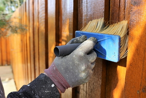 hand brushing on clear finish to wooden fence