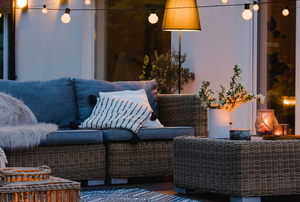 natural wicker furniture on a patio or deck with string lights
