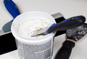 A bucket of spackle with a putty knife in it and another putty knife on the floor next to the bucket