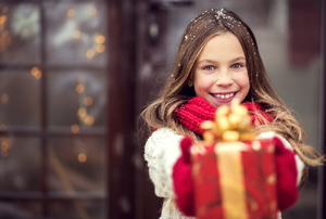 A young girl holding a red present.