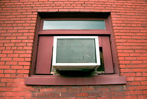 Air conditioner sitting in window, surrounded by brick