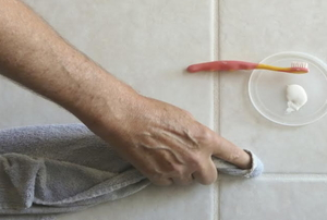 A man sealing the grout between floor tile.