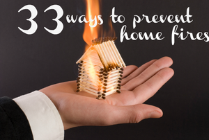 A hand holding a house made of matchsticks that are on fire.