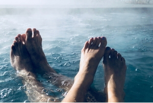 male and female feet in a steaming hot tub