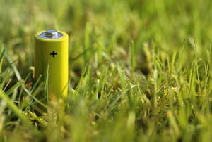 A yellow rechargeable battery sits in the grass.