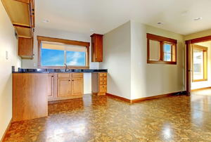 An empty kitchen with cork flooring.