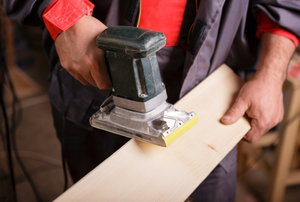 man using a sander to sand the edge of a board