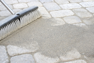 brush moving paver sand into walkway