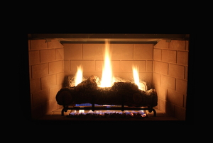 A gas fireplace lit in a dark room.