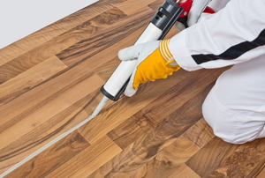 Silicone glue is applied on home flooring.