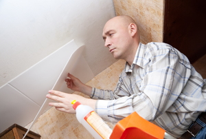 A man on a ladder installing tiles on the ceiling.