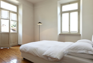 A spare bedroom painted white and filled with light.