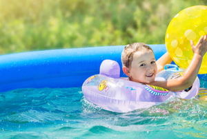 kid playing in inflatable pool with inflated toys