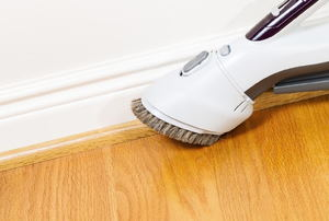 White baseboards against a tan wall and wood flooring.