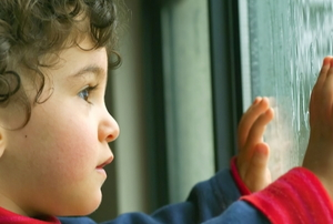 Child with hands on a window, looking out.