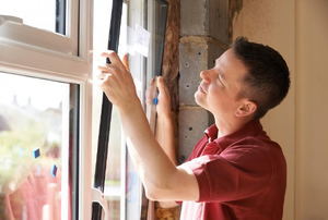 A man replacing a window in a house.