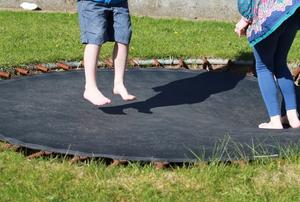 Two kids bouncing on a sunken trampoline.