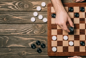 hands playing checkers on a wooden table