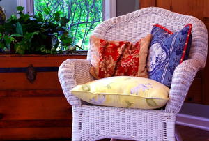 A white, wicker chair covered in throw pillows.