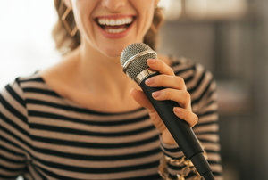 A close-up of a woman singing karaoke into a microphone.