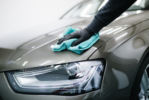 someone shining a grey car with a blue cloth