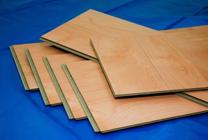 Slats of laminate flooring laying in a pile on a blue cloth.