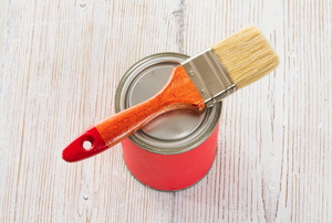A paintbrush on top of a can of lacquer finish.