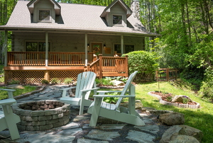 A cabin in the woods with three adirondack chairs around a fire pit.