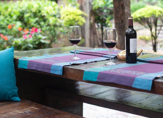 backyard patio with dark wooden table, wine glasses and bottle, and blue and purple fabrics