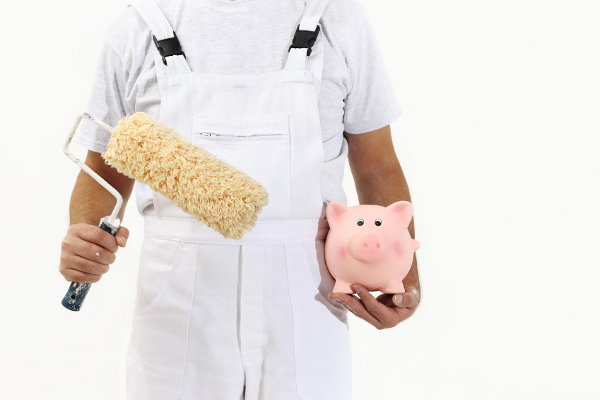 A painter in white overalls holding a piggy bank and a paint roller.