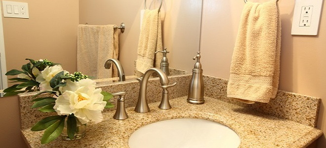 bathroom sink area with hand towel on ring