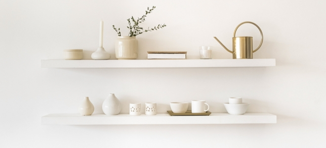floating shelves with simple ceramic items and brass watering can