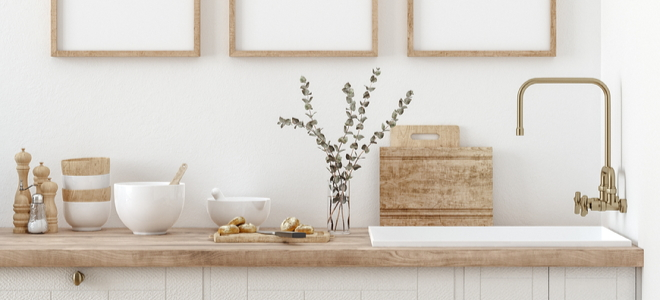 rustic kitchen decor items like salt and pepper grinders, dishes, leaves, and cutting boards on a wooden sink counter
