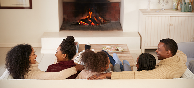 A happy family sitting on a couch in front of a fireplace