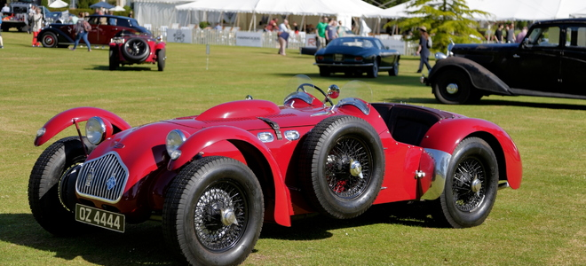 an old fashioned red race car with an extra tire on the side