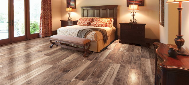 A bedroom with wood-look tile floors.