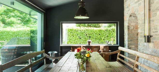 A rustic dining room with a brick wall and wood table