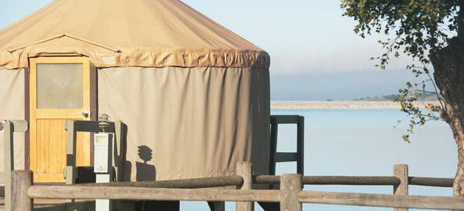 A Yurt With A Body Of Water In The Background.