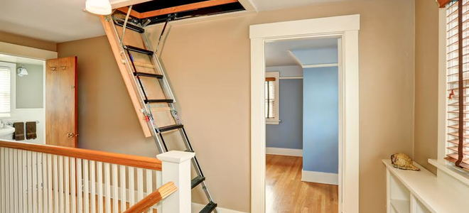 A ladder leading up to attic access in a ceiling.