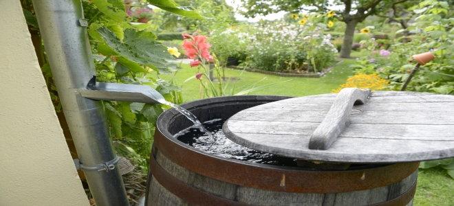 Дождевая бочка с водой, стекающей в нее из желоба.